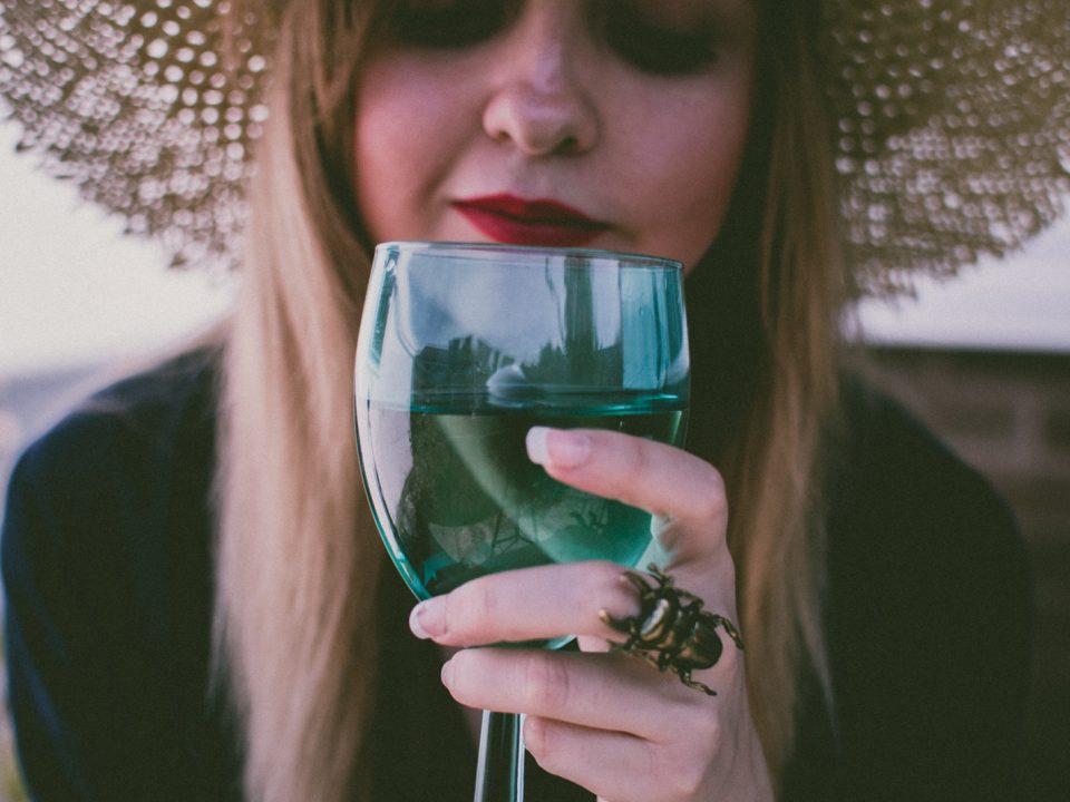 Junge Dame mit einem Strohhut hat ein gefülltes Glas vor sich und riecht daran