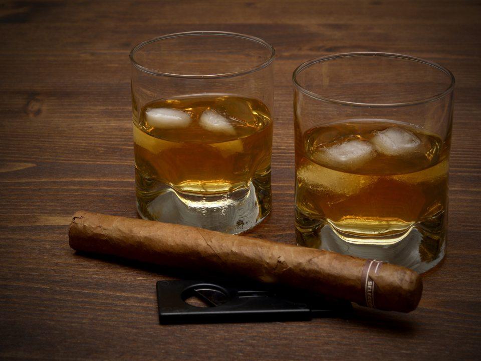 2 eckige Whiskygläser gefüllt mit Whisky und Eiswürfel. Davor liegt eine Zigarre