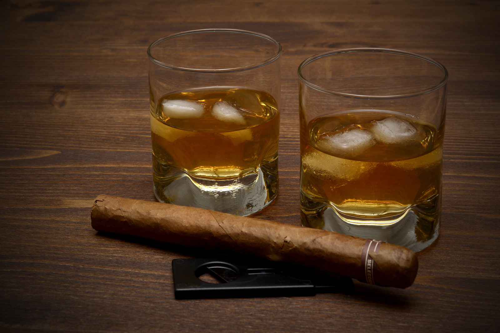 2 square whiskey glasses filled with whiskey and ice cubes. In front of it is a cigar