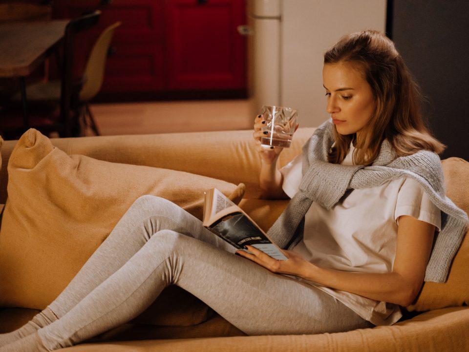 junge Dame sitzt gemütlich auf der Couch, liest ein Buch und trinkt Wein aus einem Weinglas