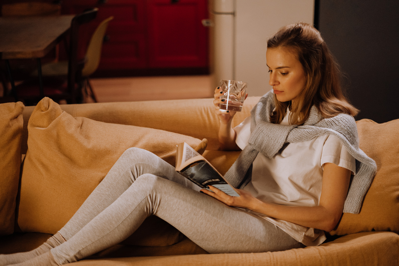 young lady sits comfortably on the couch, reads a book and drinks wine from a wine glass