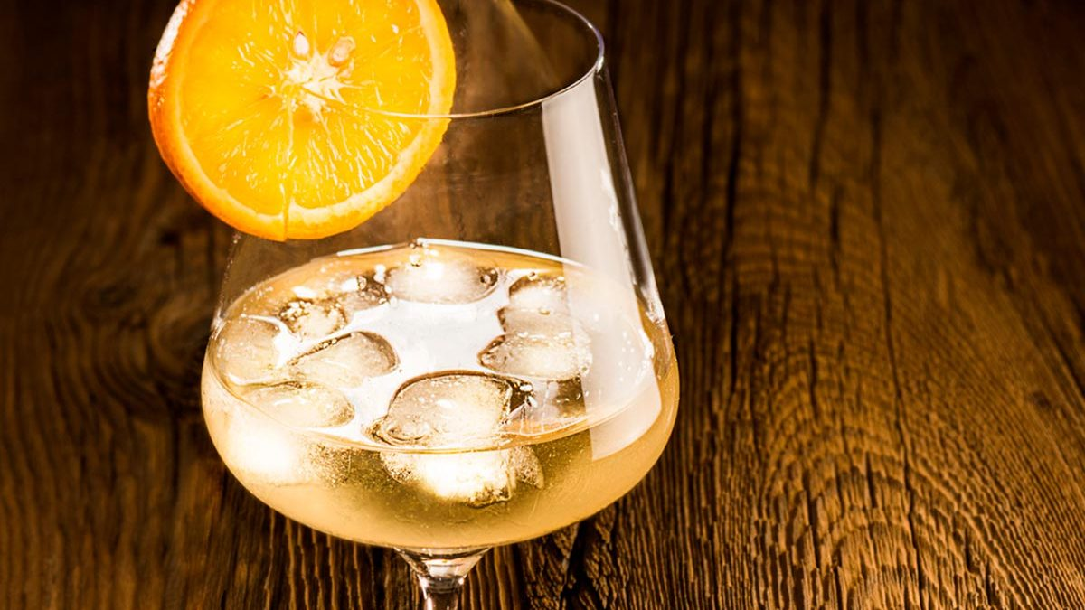 Vermouth 700 with ice cubes in a wine glass. Slice of orange as decoration, wood as background