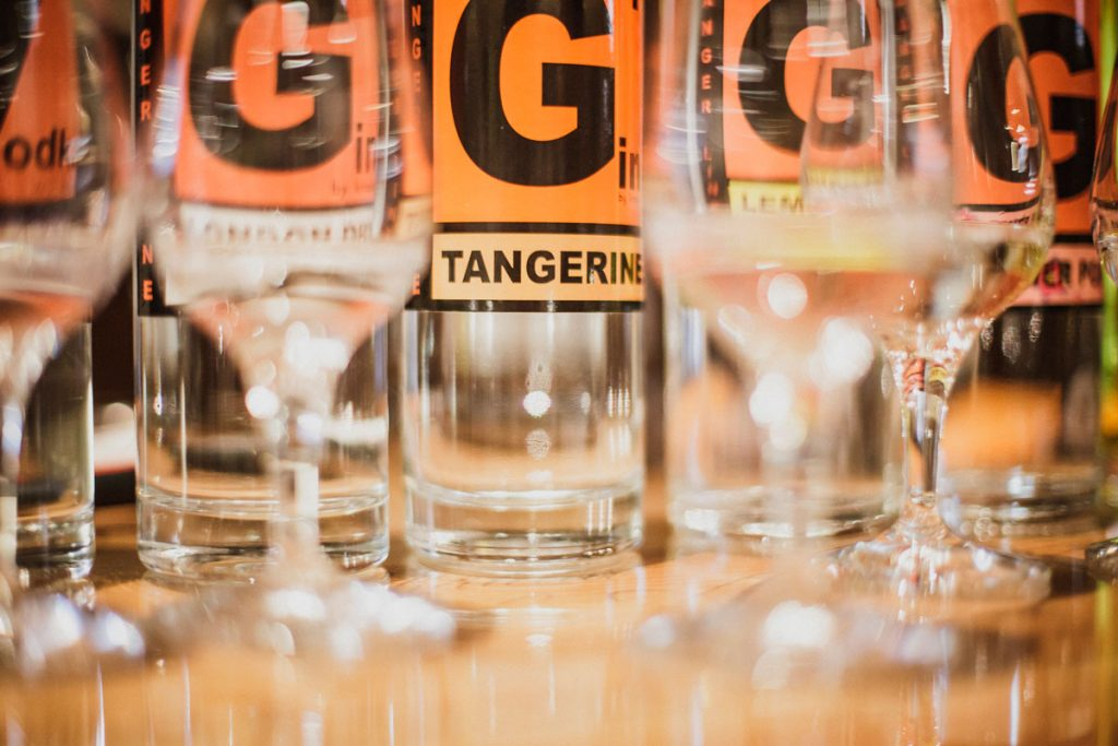 mehrere abgeschnittene G+ Gin-Flaschen. Davor sieht man verschwommene Verkostgläser stehen.