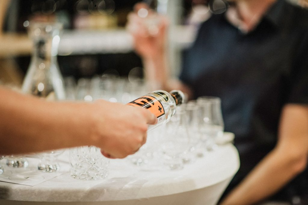 A hand pouring G+ Gin from the bottle into tasting glasses. In the background you can see a person in a dark shirt.