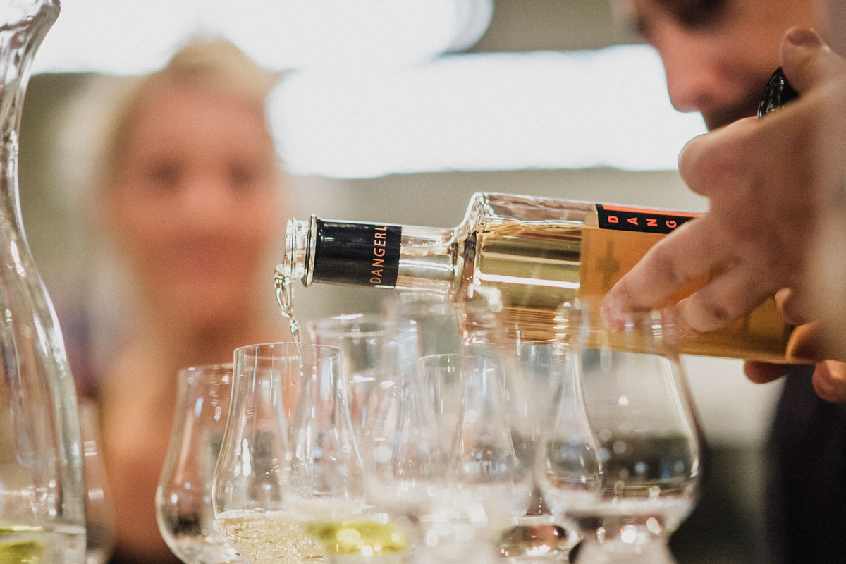 A hand pouring G+ Gin from the bottle into tasting glasses. In the background you can see a blurred, blonde lady sitting