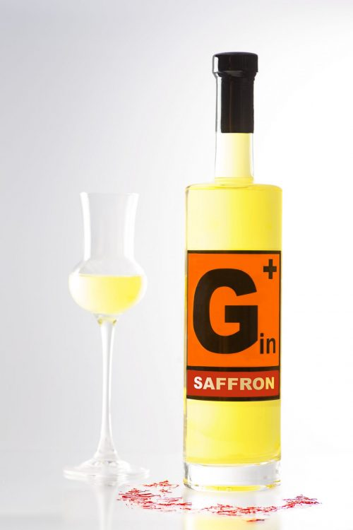Tall, slim 500ml bottle with yellow content. G + Saffron Gin. Next to the bottle is a tasting glass with yellow gin. red saffron threads lie in front of the bottle