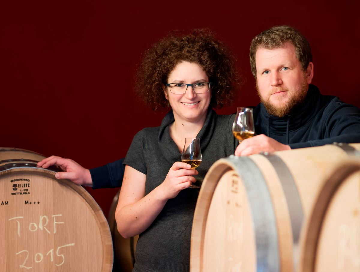 Portrait photo of Carmen Krauss and Werner Krauss between whiskey barrels. Red background, both have a tasting glass in their hands