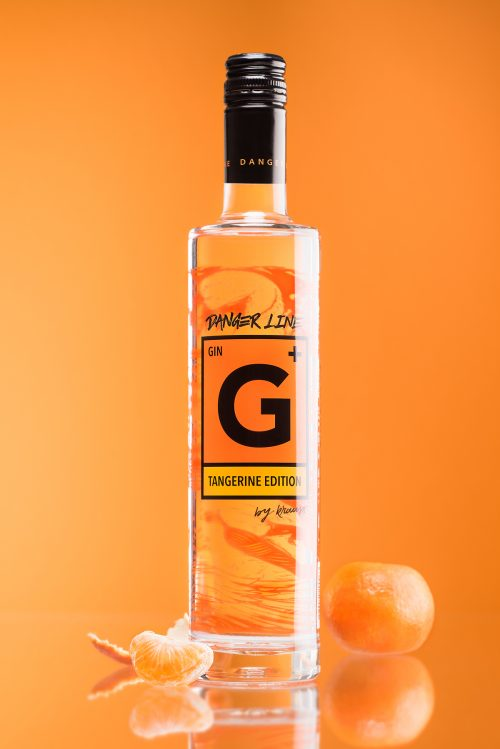 Tall, slim 500ml bottle of G+ Tangerine Edition Gin. The label is the danger sign. orange background. a whole mandarin and a mandarin column as decoration