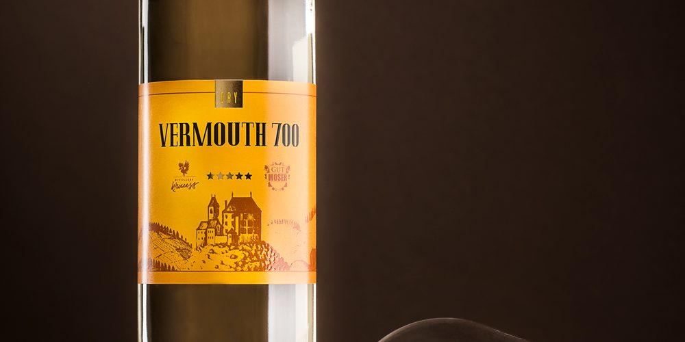 hohe, schlanke 750ml-Flasche gefüllt mit weißem Wermut. Dunkler Hintergrund, liegendes, leeres Weinglas als Dekoration, Vermouth 700