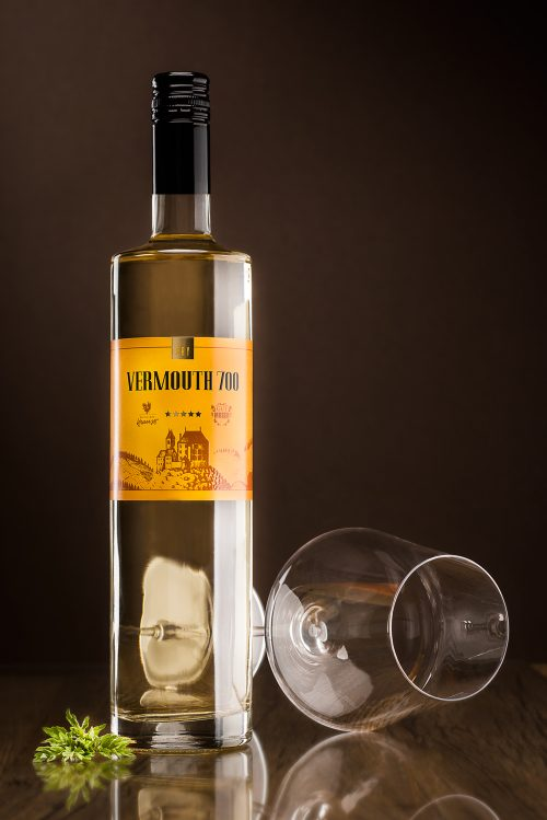 Tall, slim 750ml bottle filled with white vermouth. Dark background, lying, empty wine glass as decoration, Vermouth 700