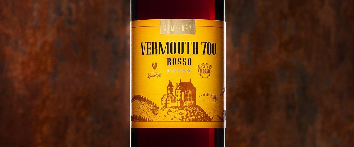 hohe, schlanke 750ml-Flasche gefüllt mit rotem Wermut. Dunkler Hintergrund, Blutorangenscheibe als Dekoration, gelb-oranges Etikett, Vermouth 700 Rosso