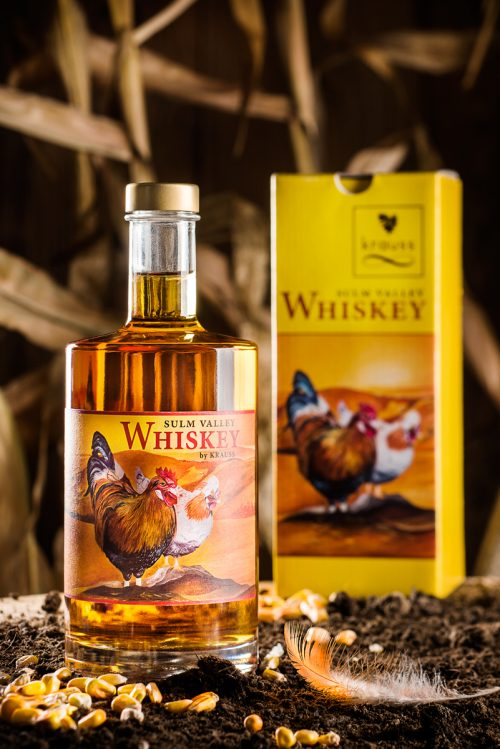 500ml whiskey bottle with a yellow label and two chickens on it. yellow cardboard in the background. Earth, corn kernels and chicken feather as decoration. Sulm Valley Whiskey