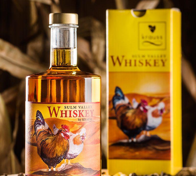 500ml Whisky Flasche mit gelbem Etikett mit zwei Hühnern drauf. gelber Karton im Hintergrund. Erde, Maiskörner und Hühnerfeder als Dekoration. Sulm Valley Whiskey