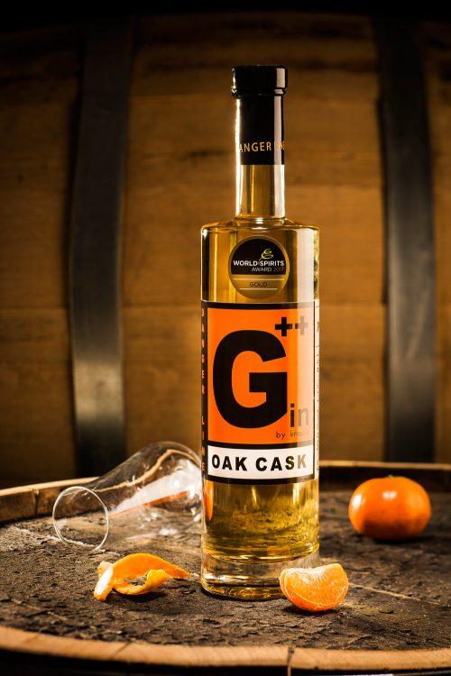 Flaschenfoto einer 0,7l Gin Oak Cast Flasche der Distillery Krauss mit Orangen als Dekoration auf Holzfass