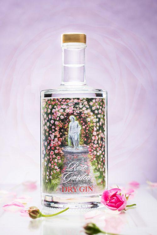 500ml Flasche Rose Garden Dry Gin vor rosarotem Hintergrund. Rosenblüten als Dekoration. Das Etikett der Flasche zeigt einen Rosengarten und eine Skulptur