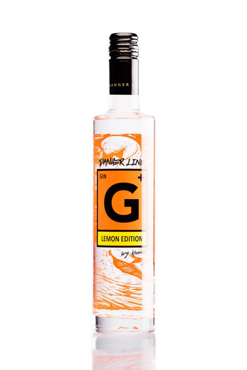 Krauss G+ Danger Line Lemon Edition gin bottle, tall bottle with clear liquid, orange danger sign as logo, orange swan illustration in the background