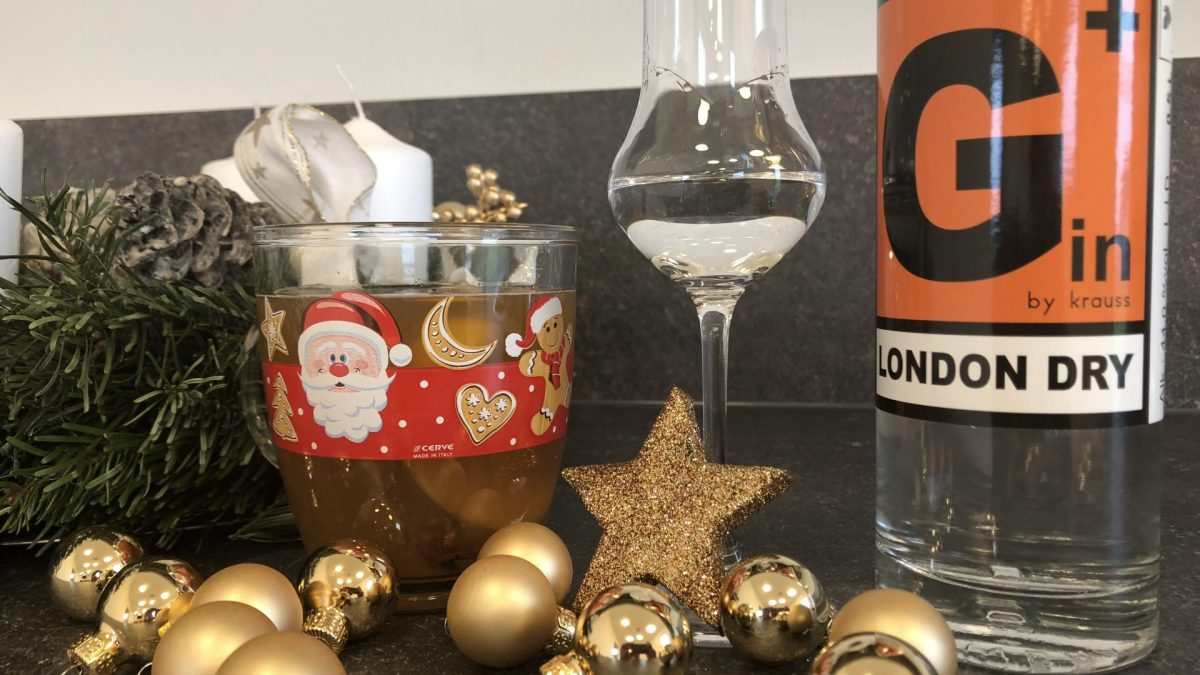 Advent wreath, golden Christmas decoration, mulled wine in a cup, tasting glass with gin and a bottle of G Plus Krauss gin