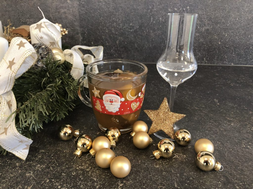 Advent wreath, mulled gin in cup, Christmas decoration and tasting glass with gin