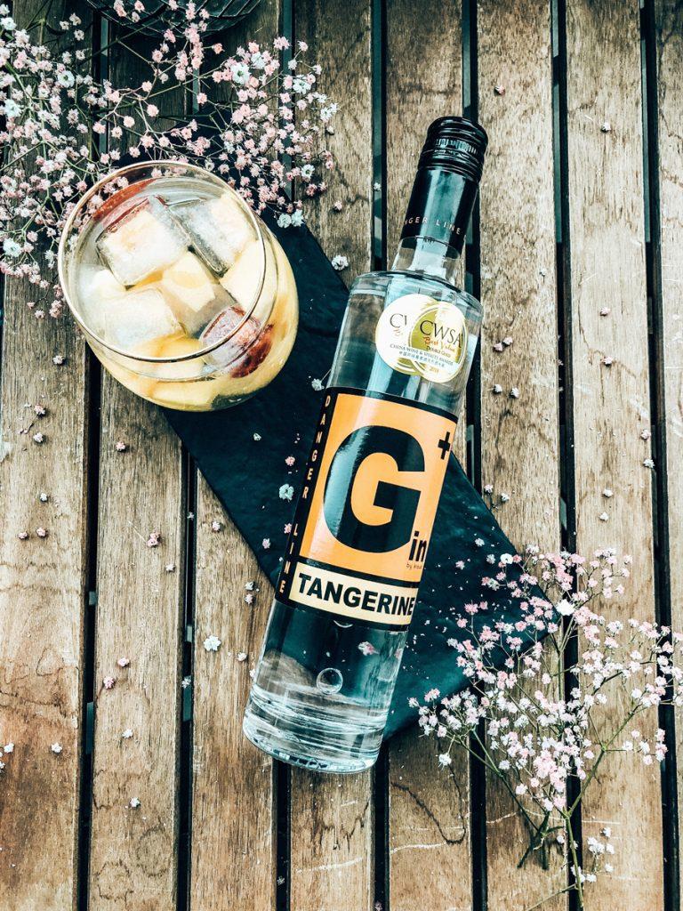 liegende, schlanke G+ Gin Flasche Tangerine mit CWSA Doublegold Medaille, daneben gefülltes Glas mit Eiswürfeln, Blümchen als Dekoration