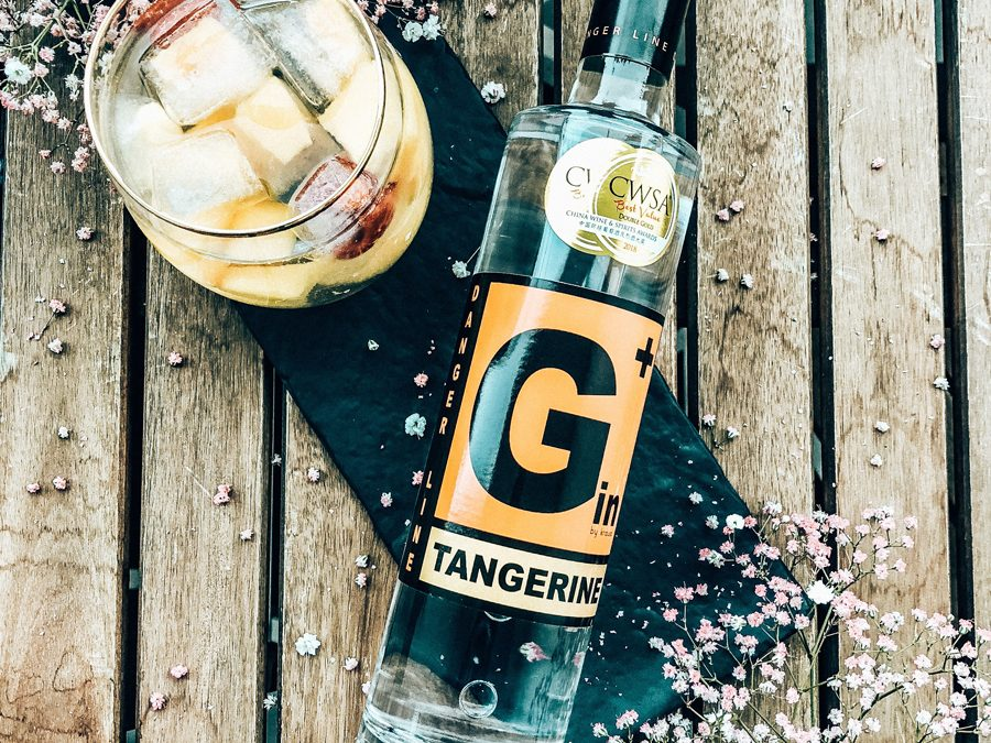 Lying, slim G+ Gin bottle of tangerine with CWSA double gold medal, next to it filled glass with ice cubes, flowers as decoration