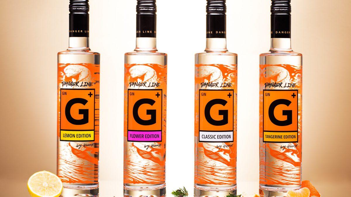 4 tall, slim bottles of Danger Line Gin from the Distillery Krauss, lemons, lavender, juniper and mandarins as decoration