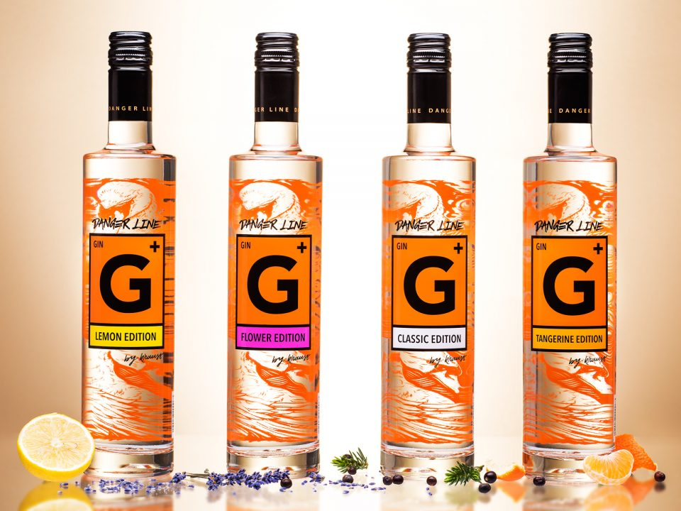 4 tall, slim bottles of Danger Line Gin from the Distillery Krauss, lemons, lavender, juniper and mandarins as decoration